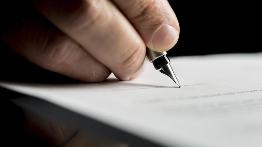 mano che scrive un documento con la penna, primo piano