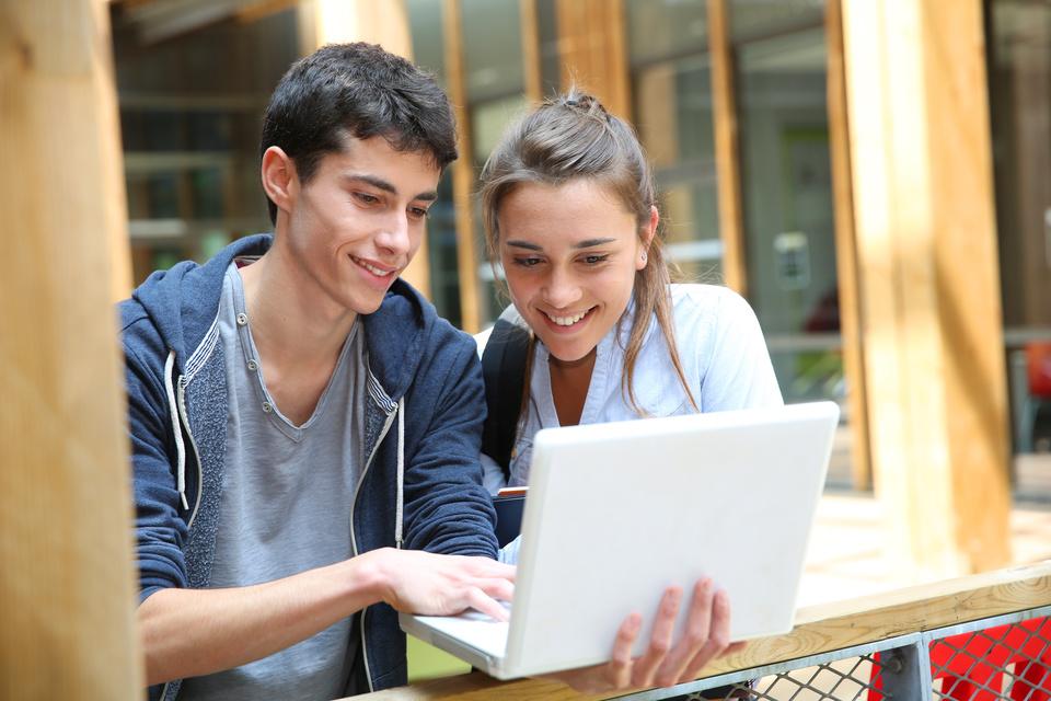 Teenagers working on laptop in school campus