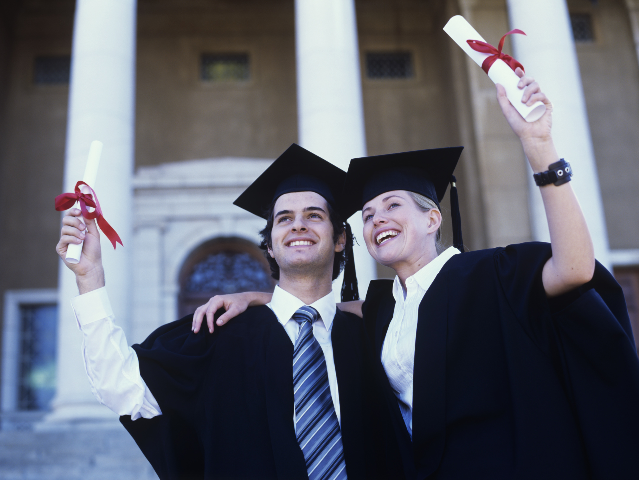 Young graduate couple outside holding scolls, smiling, low angle